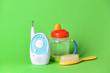 Leinwandbild Motiv Modern baby monitor with brush and bottle on color background
