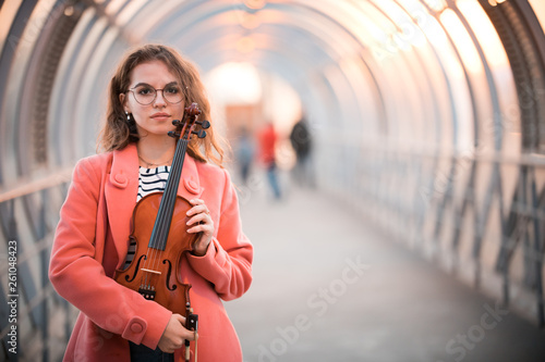 Young woman in glasses standing on the upper pedestrian crossing in a sunset holding a violin - 261048423