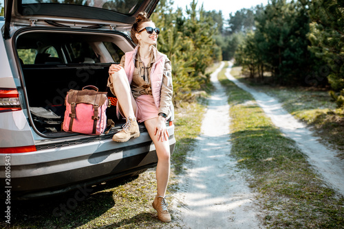 Young woman enjoying nature while sitting in the car trunk on a picturesque road in the woods - 261055431