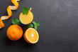 canvas print picture - A group of oranges and a glass of juice on a dark background.