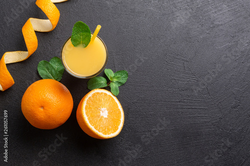canvas print picture A group of oranges and a glass of juice on a dark background.