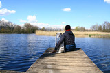 un homme et son chien assis sur un ponton