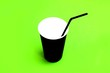 Leinwandbild Motiv paper cup of black color with a cocktail tube on a green background