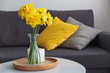 Quadro Yellow spring flowers in a vase standing in the living room on the coffe table
