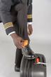London, UK. April 2019. Airline pilot brushing his black uniform shoes.
