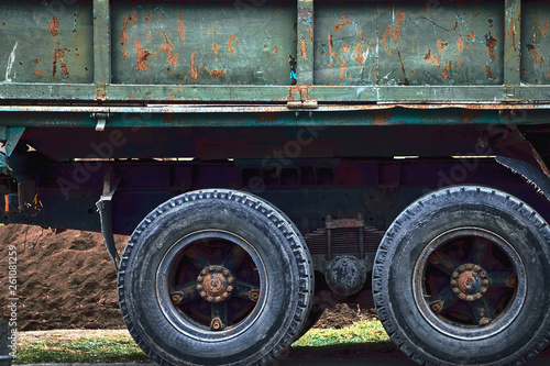 Wheels tires of an old rusty truck on the road close up.