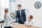 cheerful man in glasses shaking hands with recruiter on job interview