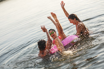 Group of friends swimming and having fun in the lake.Female sitting on air mattress drinks lemonade and having fun with friends.