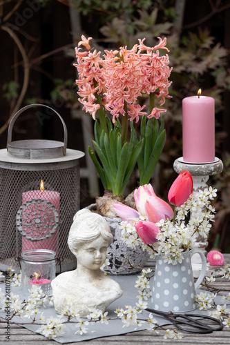 canvas print picture Gartendekoration im Frühling mit Damenbüste, Kerzen und Blüten in Pink und Weiß