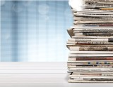 Pile of printed newspapers on blue background