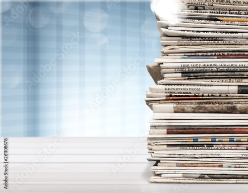 Leinwandbild Motiv Pile of printed newspapers on blue background