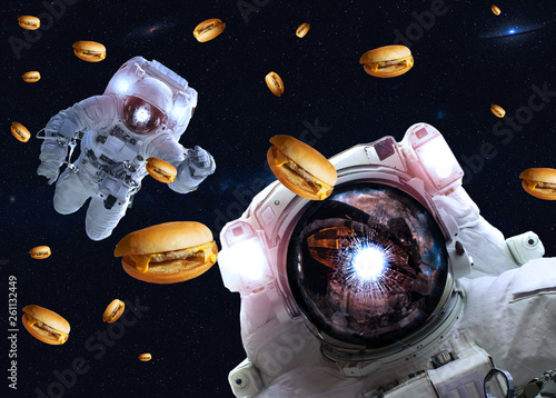 Astronauts in outer space with cheseburgers. Elements of this image furnished by NASA. Suitable for any purprose use