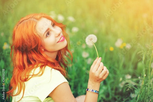 canvas print picture Portrait of young redhair woman blowing dandelion with joy in spring garden. Springtime Beautiful girl at sunset in meadow landscape. Allergic to pollen of flowers. Spring allergy free healthy concept