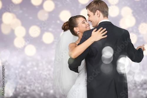 Leinwandbild Motiv Happy just married young couple dancing on blurred background