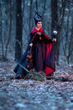 Charming and Beautiful Maleficent Woman with Highbred Dog on Leash. Posing Together in Early Spring Forest.