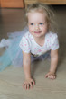 canvas print picture - Little girl crawling on the floor and smiling