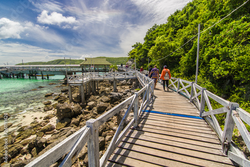 The wooden bridge, walk the beach, go to the pier to transport tourists on the island. Trees on the road on a clear day