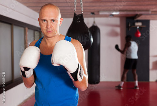 Portrait of boxer wearing gloves at boxing hall