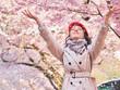Leinwandbild Motiv Beautiful happy woman enjoying smell in a flowering spring garden