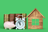 The small pink piggy bank, pile of coins, white alarm clock and wooden house on green background. Time to save money on new housing.