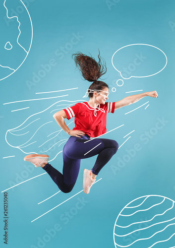 Hurry up to save the universe. Dreaming about cosmonaut profession or travel the cosmos. Young woman in drawing imaginary spacesuit against blue background. Concept of childhood and dreams.