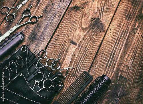Leinwanddruck Bild Stylish professional barber scissors on vintage wooden table, hairdresser salon concept, hairdressing tool set. Haircut accessories