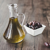 Olive oil in a glass jug on a brown wooden background. Healthy Food. Mediterranean Kitchen.