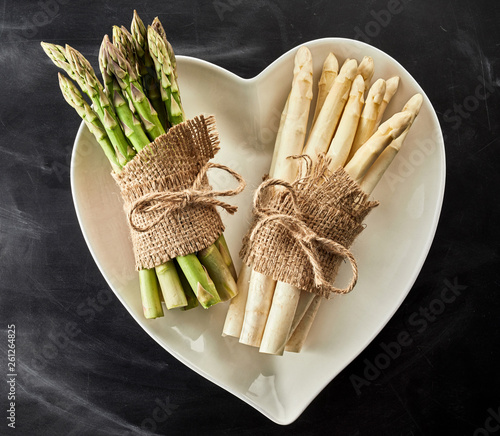 Heart shaped bowl with fresh asparagus spears - 261264825