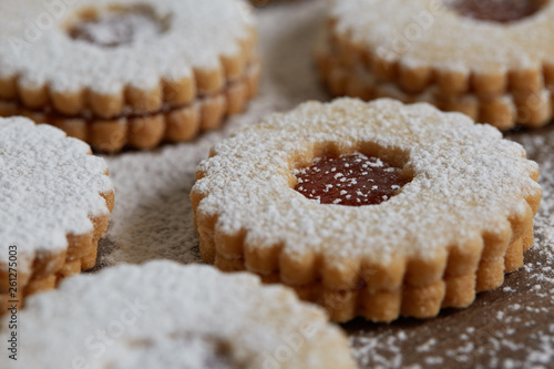 Close up of freshly baked homemade Christmas sugar cookies with jam on a wooden background © lukasvetic