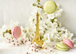 The Eiffel Tower figurine among white cherry flowers and sweet multicolored macaroons. Love, romance, spring.
