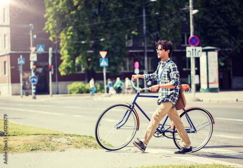 Leinwanddruck Bild people, style, city life and lifestyle - young hipster man with shoulder bag and fixed gear bike crossing crosswalk on street