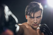 Selective focus of concentrated boxer in boxing gloves training and looking at camera on black