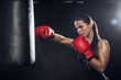 Female boxer in red boxing gloves training with punching bag on black