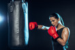 Tired boxer in red boxing gloves training with punching bag on black