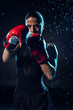 Concentrated boxer in red boxing gloves standing under water drops on black