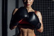 Cropped view of muscular woman in black boxing gloves