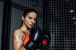 Sporty boxer in boxing gloves standing near wire netting and looking at camera
