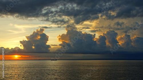canvas print picture Sonnenuntergang mit gelb angestrahlten und konturenreichen Wolken über dem Meer