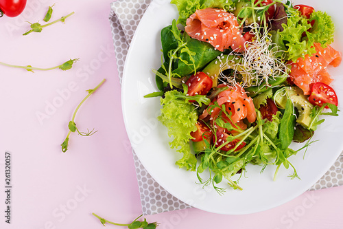 Diet menu. Healthy salad of fresh vegetables - tomatoes, avocado, arugula, seeds and salmon on a bowl. Vegan food. Flat lay. Top view - 261320057