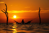 beautiful young woman silhouette with swing posing in the sea on sunset, maldivian romantic scenery