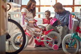 Young father and mother shopping new bicycle for little child in bike shop.