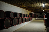 wine wooden barrels inside the undeground tunnels of a winery