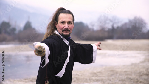 Man in black kimono pointing sword towards the camera © Video_StockOrg