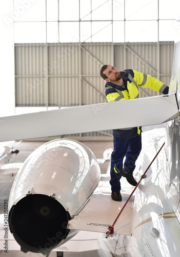 Airport workers check an aircraft for safety in a hangar