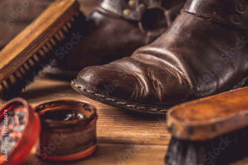 canvas print picture Old vintage leather boots with shoe brush on wooden background