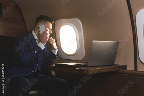 Leinwandbild Motiv attractive and successful businessman in an expensive suit working sitting in the chair of his private jet.