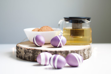 lilac Easter eggs on wooden stand with tea and cookies
