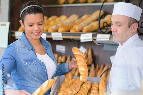 man and woman selling fresh loaves in bakery © auremar