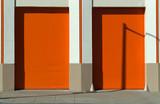 Orange doors and garage with masonery frame and wall sidewalk