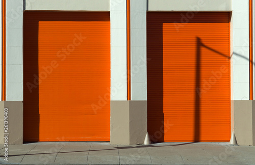 canvas print picture Orange doors and garage with masonery frame and wall sidewalk